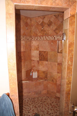 Bathroom renovated shower with frameless glass & limestone tiles