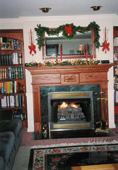 Oak mantel with dentil crown, fluted pilasters rosettes, and matching built-ins
