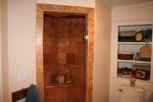 Remodeled bathroom with niche cabinet and large limestone shower