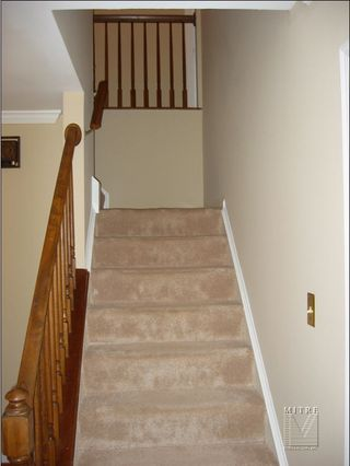 Before picture-showing carpeted treads, plain walls, pine rails