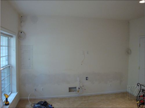 Space before built-in cabinetry installation, after electrician has wired for components and cooler