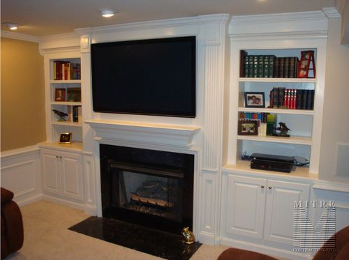 Built-In cabinets either side of fireplace, each with closed storage and roll out dvd trays.