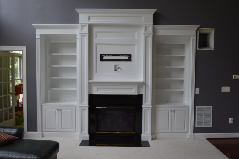 Fireplace surround with pilasters, mantel, built-in cabinetry