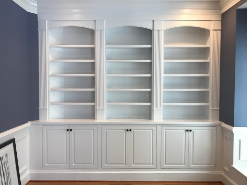Built-in cabinetry with arched bookcases